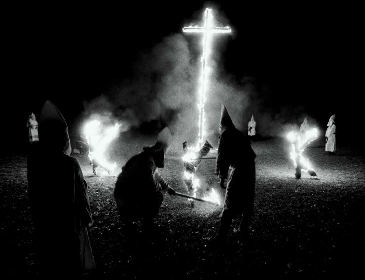 Ku Klux Klan members of South Mississippi Knights and Mississippi White Knights participate in a cross-lighting ceremony following a wedding ceremony in Petal, Miss., Dec. 31, 2001. The United States Supreme Court ruled Monday, April 7, 2003, that states can punish Ku Klux Klansmen and others who set crosses afire, finding that a burning cross is an instrument of racial terror so threatening that it overshadows free speech concerns. (AP Photo/James Edward Bates)