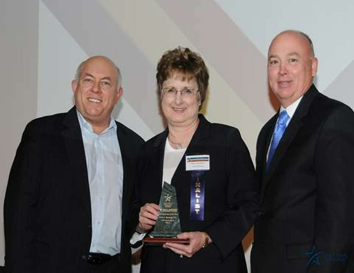 Richard Carpenter, chancellor of Lone Star College System, left, and Steve Head, president of Lone Star College-North Harris, recently presented Karen K. Abramski with the 2013 Small Business of the Year Award.