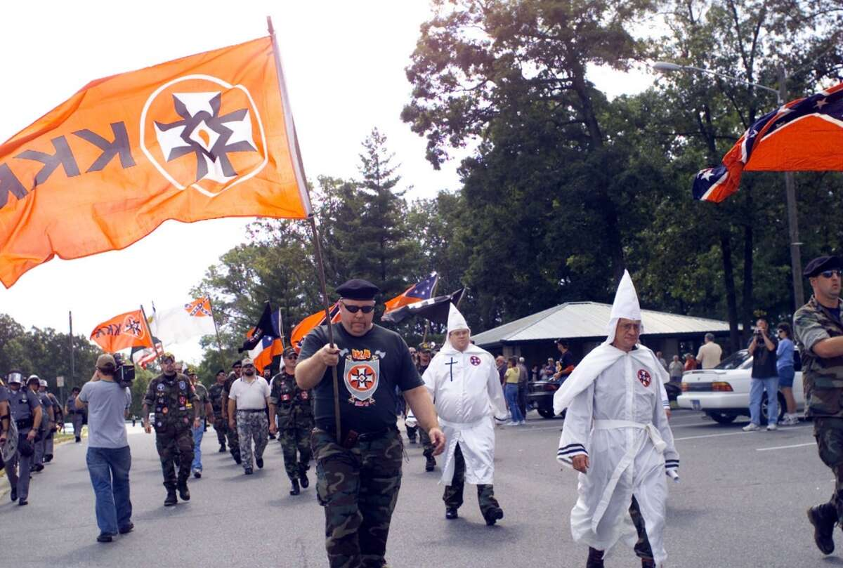 Members of the Ku Klux Klan march in Eddyville, Ky., Saturday, Sept. 27, 2003. (AP Photo/The Paducah Sun, Stephen Lance Dennee)