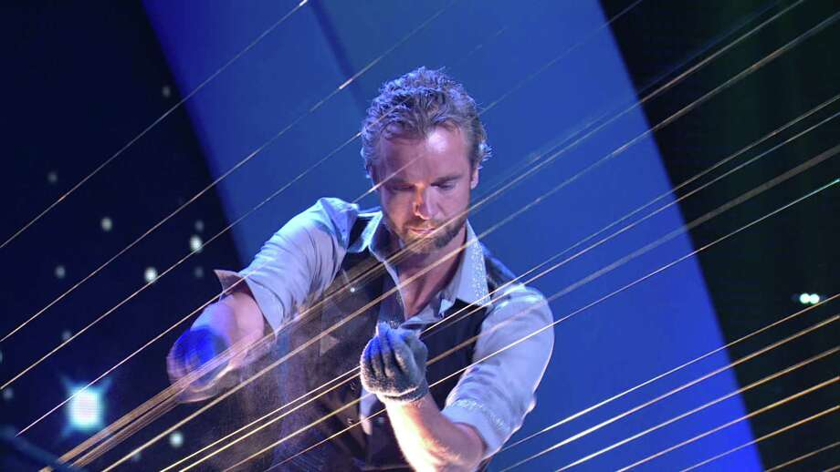 William Close plays the Earth Harp, which he designed in 1999. In its first incarnation, the strings stretched 1,000 feet across a valley. Photo: Earth Harp Collective