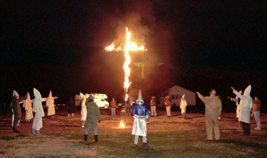 ** FILE **  Members of the Ku Klux Klan salute a burning cross in the yard of a Center Point, Ind., residence in this Nov. 4, 1995, file photo.  The freedom to burn a cross, the post-prison privacy rights of sex predators and copyright protection for lingerie will occupy the Supreme Court as the justices step from behind red velvet drapes and into their courtroom next week.  (AP Photo/Tribune-Star, Michael A. Curlett, File) Photo: AP