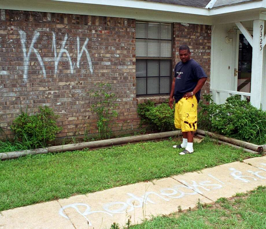 Carlos Dixon stands by the some of the spray painted graffiti on his home  in Semmes, Ala., Monday, June 10, 2002. Vandals sprayed ``KKK,'' ``cotton pickers'' and ``slaves'' on the home and property of Dixon who moved into a racially mixed neighborhood four months ago and flew the American flag out front. (AP Photo/Mobile Register, Ron Colquitt) Photo: AP