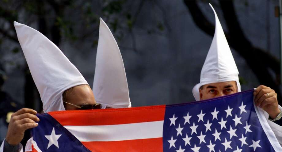 Ku Klux Klansmen use a flag to help conceal their identities during a rally held outside the Criminal Court Building Saturday, Oct. 23, 1999 in New York. While they won a permit to rally through the courts, they were denied permission to wear their trademark masks.  (AP Photo/Bebeto Matthews)  HOUCHRON CAPTION (10/24/1999):  Ku Klux Klansmen use a flag to help conceal their identities during a rally Saturday in New York. Photo: AP