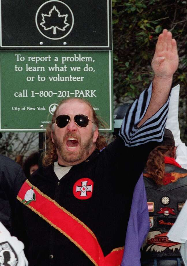 Jeffrey Berry, national imperial wizard of the American Knights of the Ku Klux Klan, salutes while saying 'white power,' as Klan members are escorted by police from a rally held in New York, Saturday, Oct. 23, 1999. After days of legal maneuvering about their rights to rally, KKK members stood silently inside a pen fashioned from police barricades on Saturday and faced the jeers of thousands of protesters. (AP Photo/David Karp) Photo: AP