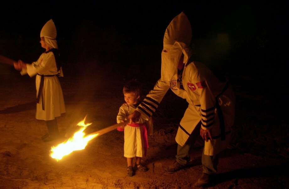 KRT US NEWS STORY SLUGGED: KUKLUXKLAN-2 KRT PHOTOGRAPH BY TIM ISBELL/BILOXI SUN HERALD (June 12) Art Dixon helps his son, Artis Floyd Dixon Jr., hold a burning stake as they circle a cross during a cross lighting in Pearl, Mississippi on August 26, 2001. (BI) NC KD 2002 (Horiz) (lde) Photo: KRT