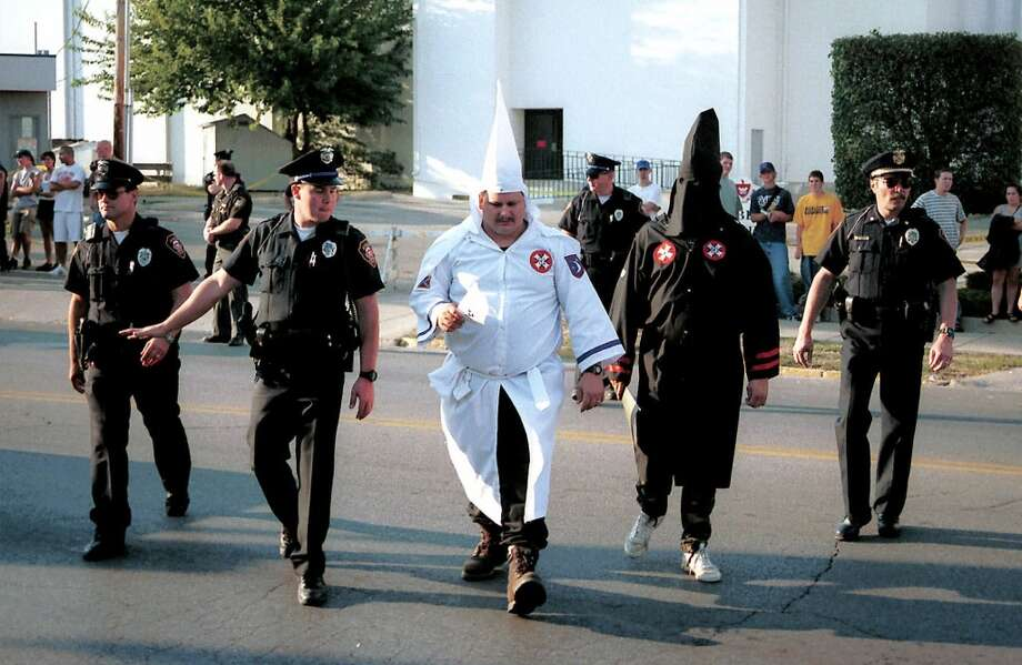 FILE--Police officers escort robed Ku Klux Klansmen across the street in Piqua, Ohio, before the start of a rally at the courthouse Saturday, Sept. 25, 1999. KKK rallies have cost communities as much as $800,000 this year in increased security. (AP Photo/Piqua Daily Call, Robert Moorhead, File) Photo: AP