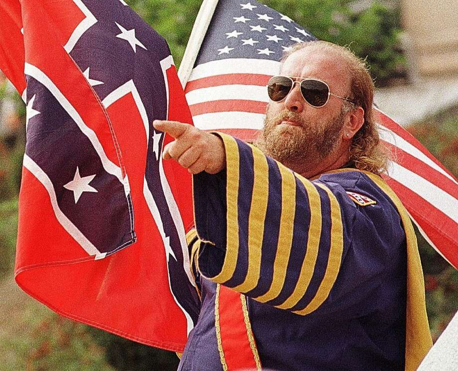 An unidentified member of the Ku Klux Klan holds a Confederate flag and American flag while taunting the crowd on the steps of the Schuylkill County Courthouse, Saturday, Sept. 26, 1998, in Pottsville, Pa. The American Knights of the Ku Klux Klan were confronted throughout their one-hour rally with spectators holding up anti-KKK signs and yelling obscenities as the 26 Klan members spoke.( AP Photo/Johnathan Paroby) Photo: AP