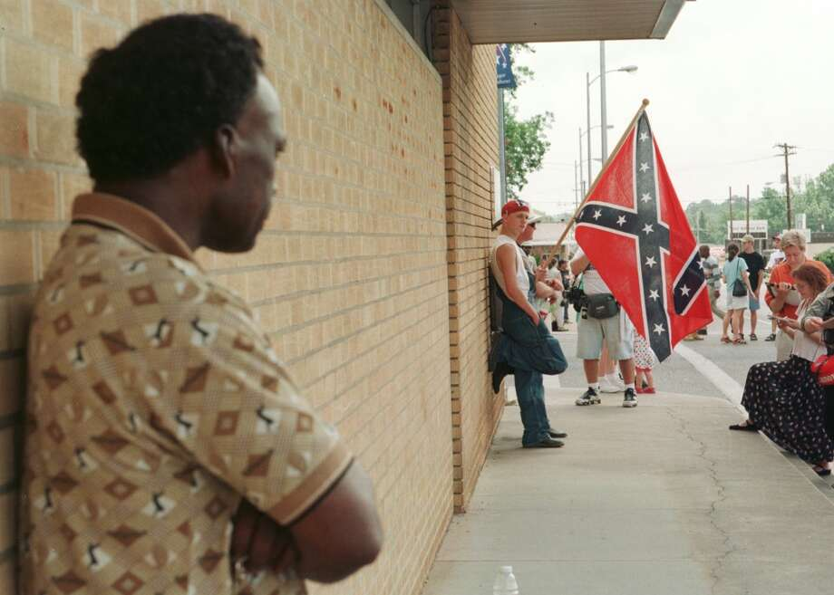 DRAGGING DEATH -- K.C. Adams of Jasper watches Ku Klux Klan member. Jasper. Ku Klux Klan rally  06/27/98.  HOUCHRON CAPTION (06/28/1998): K.C. Adams of Jasper, left, exchanges a glance with a 17-year old Ku Klux Klan member holding a Rebel flag, who would identify himself only as John of Cleveland, as he talks with the media before the KKK rally in front of the jasper County Courthouse on Saturday.   HOUCHRON CAPTION (12/27/1998):  . K.C. Adams, left, of Jasper exchanges a wary glance with a 17-year-old Ku Klux Klan member before a June KKK rally in the wake of a slaying in Jasper that was thought to be racially motivated.  HOUSTON CHRONICLE SPECIAL SECTION/TEXAS MAGAZINE: LOOKING BACK REVIEW '98. Photo: Houston Chronicle