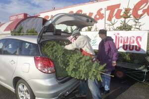 12/16/02 chubby 17 biz Chris Gaddis   Christmas tree seller for Chubby and Tubby store on Aurora Av. North in Seattle loads a Noble Fir tree for Gerda Newsheller that she bought for $l7.99, the store is for sale.