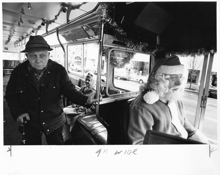 "Santa has been active in Seattle over the years. Every year, he used to turn Metro's then-free-ride bus into the ""Holiday Trolley."" Pictured are driver Larry Bach and rider Henry Bruckman on Dec. 19, 1981. Photo: -"