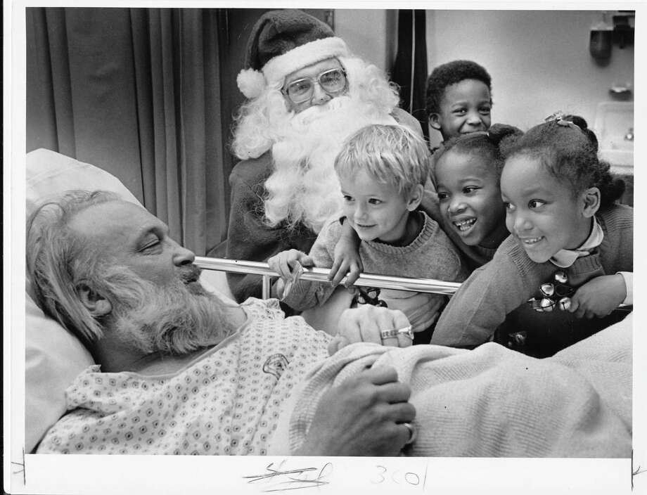 Santa and Montlake Elementary kids visit patients at the University of Washington hospital on Dec. 3, 1984. Pictured is patient Jim McEvoy, recovering from back surgery.  Photo: -
