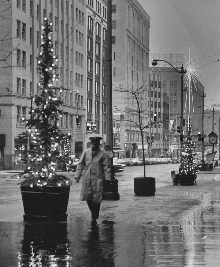 Christmas has always been a study in contrasts, from loneliness to merriment. Pictured is a lone beat cop in downtown Seattle on Christmas Eve, either in the '60s or '80s. (Smudged date stamp is illegible) Photo: -