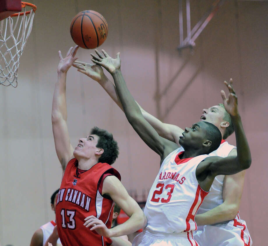 At left, New Canaan's Claude Chandonnet, Jr., (# 13), goes for a rebound along with Greenwich players, Leonel Hyatt (# 23) and Alex Wolf, right, Boys varsity basketball game between Greenwich High School and New Canaan High School at Greenwich, Wednesday night, Dec. 18, 2013. Photo: Bob Luckey / Greenwich Time