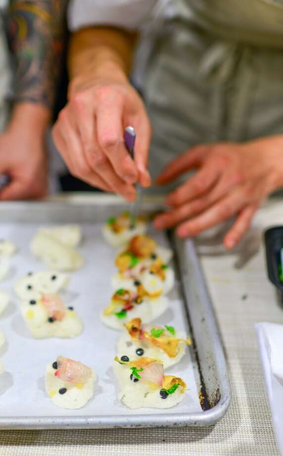 Canape: Shrimp chips, sliced aji, sunchoke chip, squid ink. Photo: Bonjwing Lee Photography