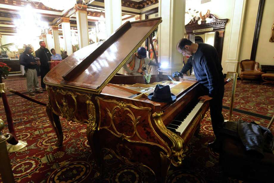 Johnny M. Verduzco, a piano tuner, works on the ornate Steinway piano that has been returned to the St. Anthony Hotel after being gone for 20 years. Ralph W. Morrison, former owner of the hotel, brought the piano to San Antonio in 1938, where it was the musical centerpiece for over 50 years. In March, hotel owners paid $220,000 to purchase it at auction. Photo: Billy Calzada, San Antonio Express-News / San Antonio Express-News