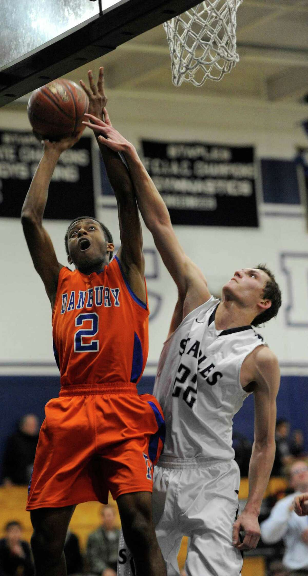 Staples high school's Nick Esposito tries to stop Danbury high school's Elijah Duffy from scoring a layup during a boys basketball game played at Staples, Westport, CT on Wednesday, December,18th, 2013.
