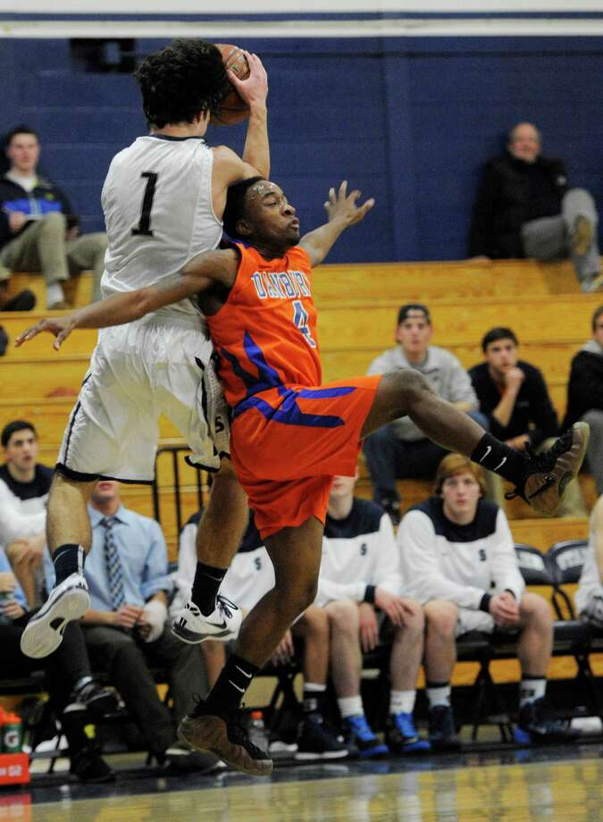 Staples high school's Jake Melnick collides with Danbury high school's Chris Latham during a boys basketball game against played at Staples, Westport, CT on Wednesday, December,18th, 2013. Photo: Mark Conrad / Connecticut Post Freelance