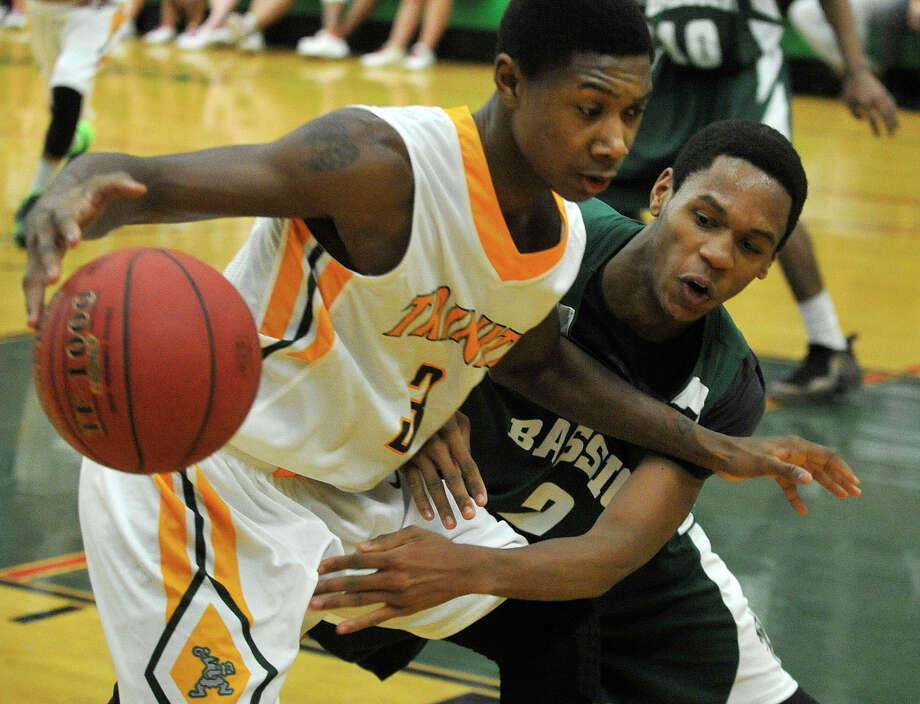 Bassick's Curhone Baldwin reaches in on Trinity Catholic's Tremaine Fraiser during their basketball game at Trinity Catholic High School in Stamford, Conn., on Wednesday, Dec. 18, 2013. Bassick beat Trinity Catholic, 63-57. Photo: Jason Rearick / Stamford Advocate