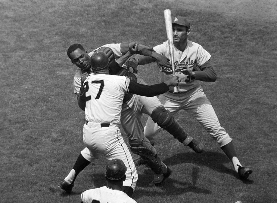 Giants pitcher Juan Marichal (27) swings a bat at Dodgers catcher John Roseboro in the third inning at Candlestick Park in San Francisco on Aug. 22, 1965. Photo: Robert H. Houston, AP