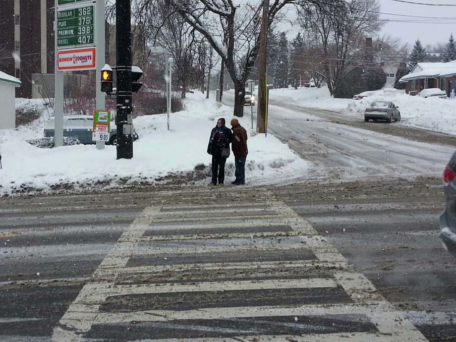 Harvey Munson and Jovahn Hotte wait in the roadway to cross Hoosick Street on Tuesday in Troy, as the Hess Express gas station failed to clear snow from the sidewalk. (Photo by Chris Churchill / Times Union)