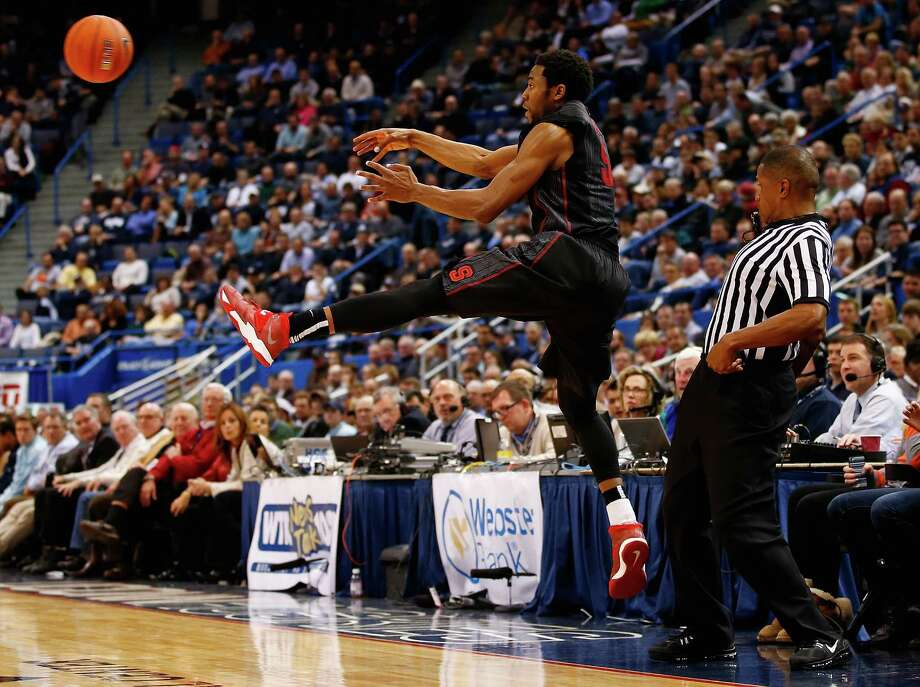 HARTFORD, CT - DECEMBER 18:  Chasson Randle #5 of the Stanford Cardinal keeps a ball in bounds in the first half against the Connecticut Huskies during the game at XL Center on December 18, 2013 in Hartford, Connecticut. Photo: Jared Wickerham, Getty Images / 2013 Getty Images