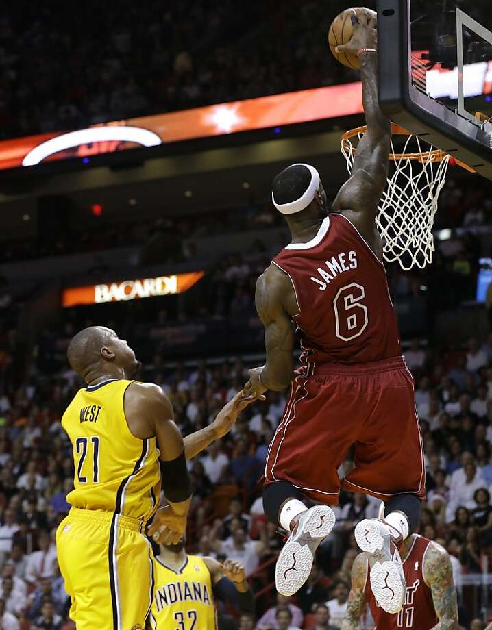 LeBron James dunks in front of David West in the second half, when the Heat rallied from 15 down in the final 18 minutes. Photo: Lynne Sladky, Associated Press