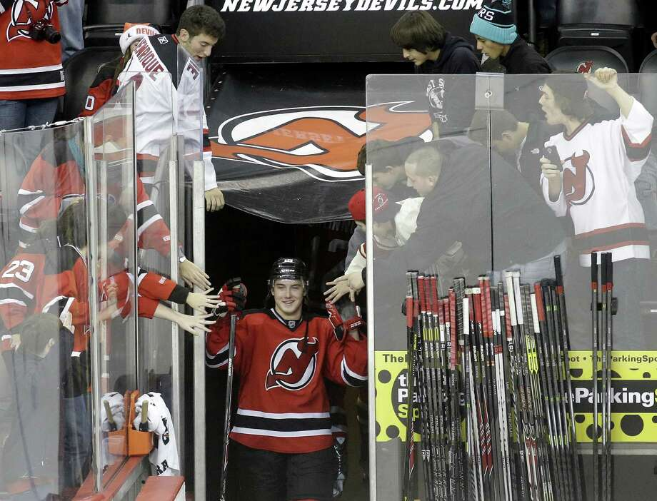 New Jersey Devils left wing Reid Boucher takes a curtain call after the Devils' NHL hockey game against the Ottawa Senators, Wednesday, Dec. 18, 2013, in Newark, N.J. Boucher scored his first career NHL goal during the Devils' 5-2 victory. (AP Photo/Julio Cortez) ORG XMIT: NJJC113 Photo: Julio Cortez / AP