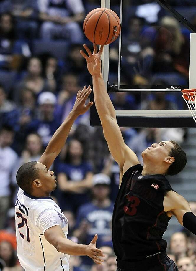 Stanford's Dwight Powell blocks a first-half shot by UConn's Omar Calhoun, a precursor to the Cardinal's take-charge second half. Photo: Fred Beckham, Associated Press