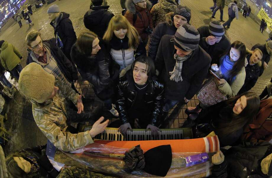 "A young man plays a piano in a street Wednesday near a pro-European Union rally in Independence Square in Kiev, Ukraine. Russian and Ukrainian leaders both pledged Tuesday to boost economic and trade ties to expand their ""strategic partnership."" Photo: Associated Press / AP"