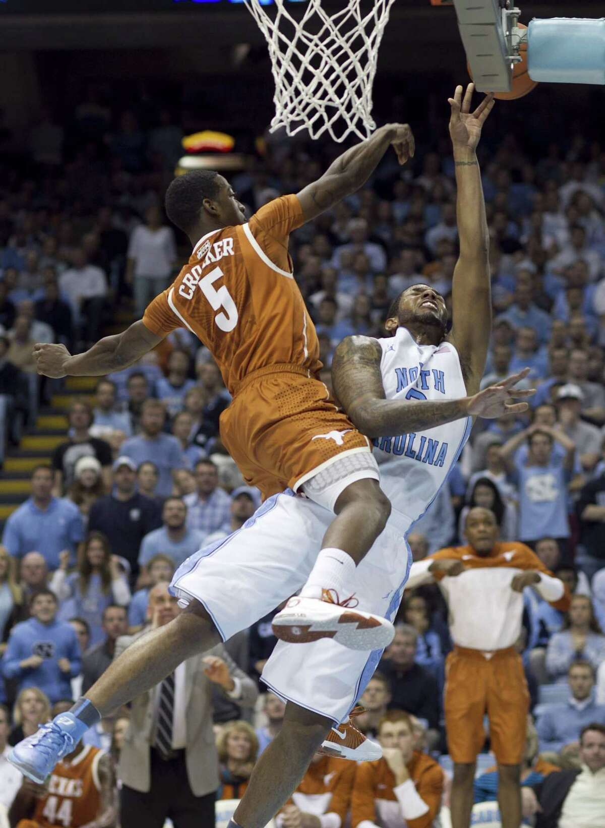 Texas' Damarcus Croaker (5) shows his leaping ability while blocking the shot of North Carolina's Leslie McDonald, but body contact results in a foul.