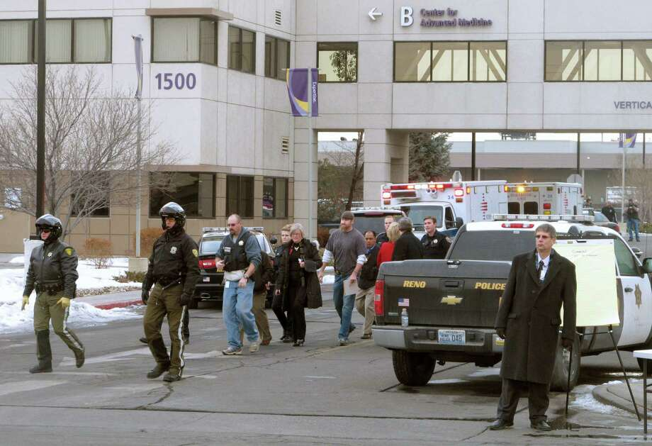 Police escort staffers and others at a medical center complex in Reno, Nev., where a gunman killed a doctor and himself. Photo: Scott Sonner / Associated Press / AP