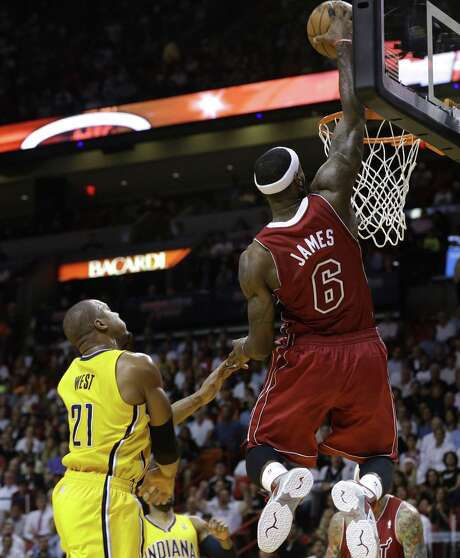 LeBron James dunks in front of Indiana forward David West after having blown past the Pacers' Luis Scola (not shown) during Miami's 97-94 victory. Photo: Lynne Sladky / Associated Press / AP