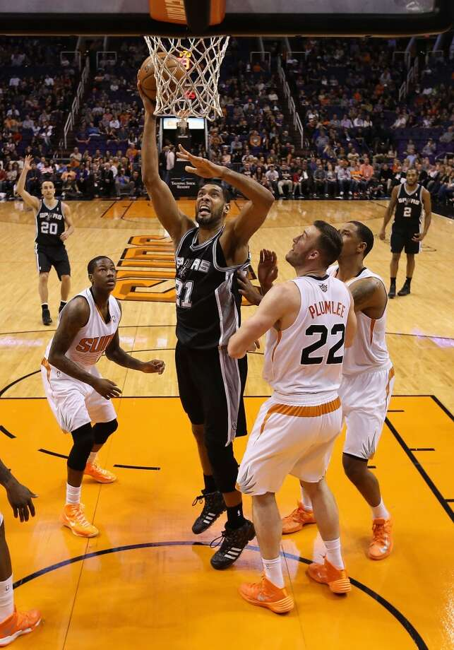 Tim Duncan #21 of the San Antonio Spurs puts up a shot over Miles Plumlee #22 of the Phoenix Suns during the first half of the NBA game at US Airways Center on December 18, 2013 in Phoenix, Arizona.  NOTE TO USER: User expressly acknowledges and agrees that, by downloading and or using this photograph, User is consenting to the terms and conditions of the Getty Images License Agreement.  (Photo by Christian Petersen/Getty Images) Photo: Christian Petersen, Getty Images