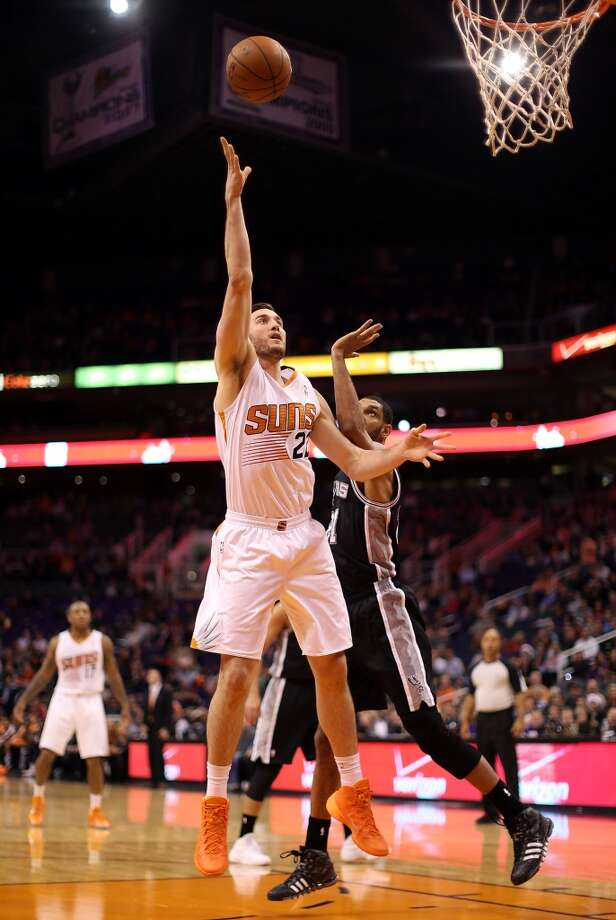 Miles Plumlee #22 of the Phoenix Suns puts up a shot past Tim Duncan #21 of the San Antonio Spurs during the first half of the NBA game at US Airways Center on December 18, 2013 in Phoenix, Arizona.  NOTE TO USER: User expressly acknowledges and agrees that, by downloading and or using this photograph, User is consenting to the terms and conditions of the Getty Images License Agreement.  (Photo by Christian Petersen/Getty Images) Photo: Christian Petersen, Getty Images