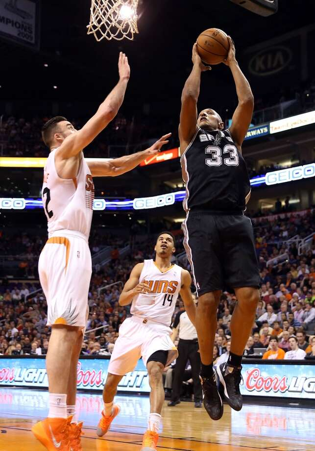 PHOENIX, AZ - DECEMBER 18:  Boris Diaw #33 of the San Antonio Spurs puts up a shot against Miles Plumlee #22 of the Phoenix Suns during the second half of the NBA game at US Airways Center on December 18, 2013 in Phoenix, Arizona.  The Spurs defeated the 108-101.  NOTE TO USER: User expressly acknowledges and agrees that, by downloading and or using this photograph, User is consenting to the terms and conditions of the Getty Images License Agreement.  (Photo by Christian Petersen/Getty Images) Photo: Christian Petersen, Getty Images