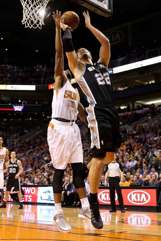 PHOENIX, AZ - DECEMBER 18:  Tiago Splitter #22 of the San Antonio Spurs puts up a shot past Markieff Morris #11 of the Phoenix Suns during the second half of the NBA game at US Airways Center on December 18, 2013 in Phoenix, Arizona. The Spurs defeated the 108-101.  NOTE TO USER: User expressly acknowledges and agrees that, by downloading and or using this photograph, User is consenting to the terms and conditions of the Getty Images License Agreement.  (Photo by Christian Petersen/Getty Images) Photo: Christian Petersen, Getty Images