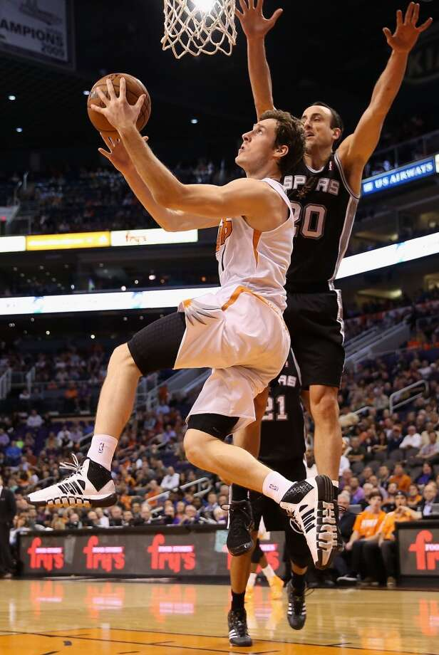 Goran Dragic #1 of the Phoenix Suns attempts a lay up shot past Manu Ginobili #20 of the San Antonio Spurs during the first half of the NBA game at US Airways Center on December 18, 2013 in Phoenix, Arizona. The Spurs defeated the 108-101.  NOTE TO USER: User expressly acknowledges and agrees that, by downloading and or using this photograph, User is consenting to the terms and conditions of the Getty Images License Agreement.  (Photo by Christian Petersen/Getty Images) Photo: Christian Petersen, Getty Images