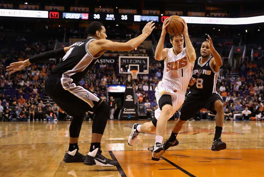 Goran Dragic #1 of the Phoenix Suns drives the ball past Danny Green #4 and Patty Mills #8 of the San Antonio Spurs during the first half of the NBA game at US Airways Center on December 18, 2013 in Phoenix, Arizona. The Spurs defeated the 108-101.  NOTE TO USER: User expressly acknowledges and agrees that, by downloading and or using this photograph, User is consenting to the terms and conditions of the Getty Images License Agreement.  (Photo by Christian Petersen/Getty Images) Photo: Christian Petersen, Getty Images