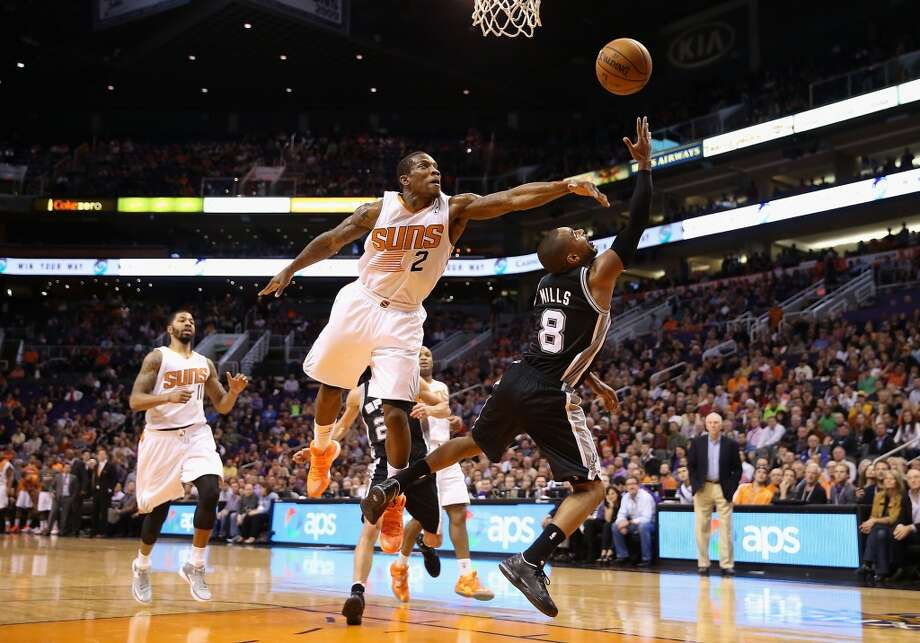 PHOENIX, AZ - DECEMBER 18:  Patty Mills #8 of the San Antonio Spurs puts up a shot past Eric Bledsoe #2 of the Phoenix Suns during the second half of the NBA game at US Airways Center on December 18, 2013 in Phoenix, Arizona. The Spurs defeated the 108-101. NOTE TO USER: User expressly acknowledges and agrees that, by downloading and or using this photograph, User is consenting to the terms and conditions of the Getty Images License Agreement.  (Photo by Christian Petersen/Getty Images) Photo: Christian Petersen, Getty Images