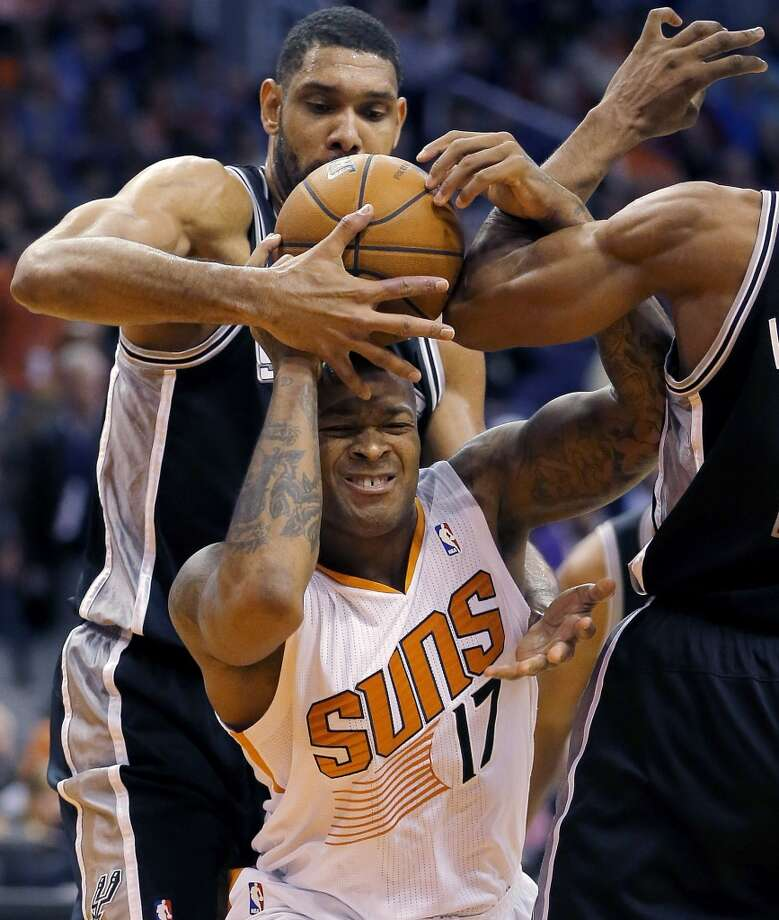 San Antonio Spurs' Tim Duncan pulls the ball away from Phoenix Suns' P.J. Tucker (17) during the second half of an NBA basketball game, Wednesday, Dec. 18, 2013, in Phoenix. The Spurs won 108-101. (AP Photo/Matt York) Photo: Matt York, Associated Press