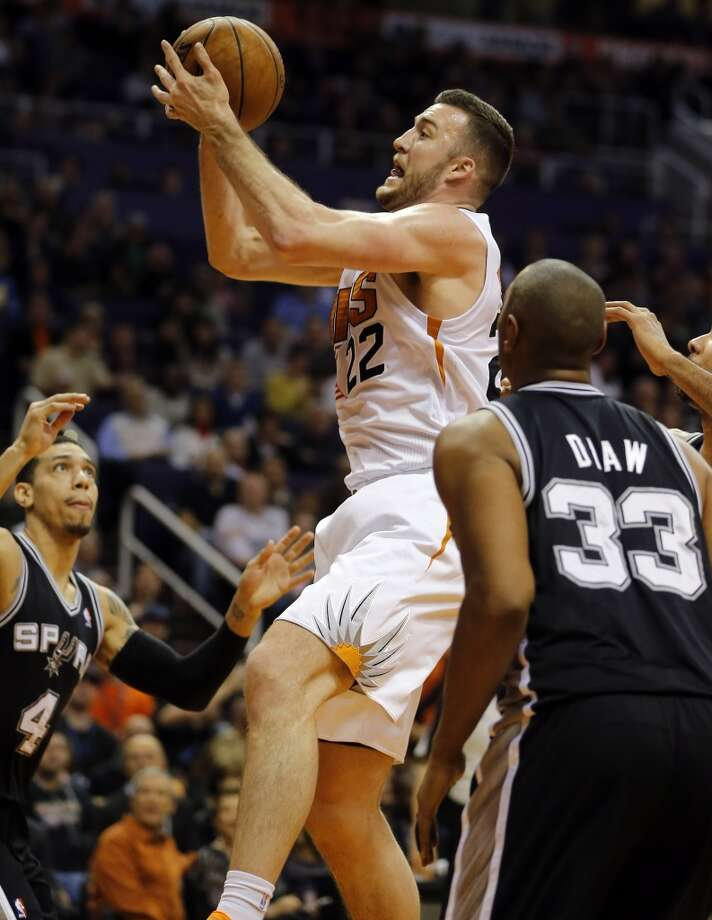 Phoenix Suns' Miles Plumlee (22) drives past San Antonio Spurs' Boris Diaw (33), of France, during the second half of an NBA basketball game, Wednesday, Dec. 18, 2013, in Phoenix. The Spurs won 108-101. (AP Photo/Matt York) Photo: Matt York, Associated Press