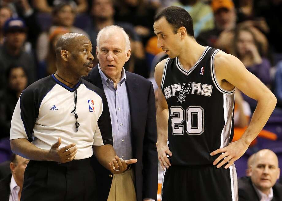 San Antonio Spurs coach Greg Popovich and player Manu Ginobili, of Argentina, talk with referee Marc Davis during the first half of an NBA basketball game against the Phoenix Suns, Wednesday, Dec. 18, 2013, in Phoenix. (AP Photo/Matt York) Photo: Matt York, Associated Press