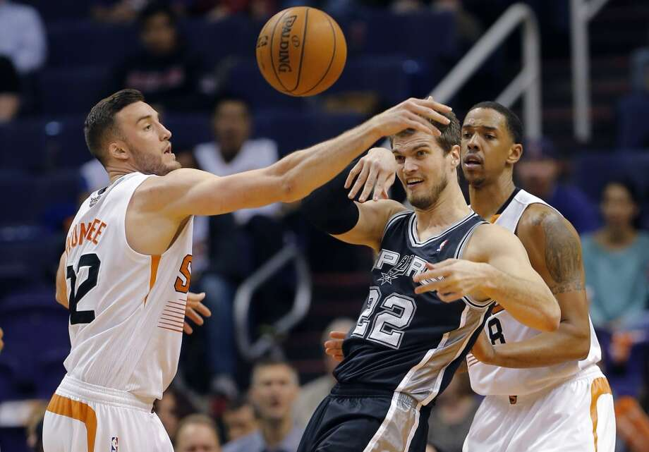 San Antonio Spurs' Tiago Spliter (22), of Brazil, passes away from Phoenix Suns' Miles Plumlee, left, and Channing Frye during the second half of an NBA basketball game, Wednesday, Dec. 18, 2013, in Phoenix. The Spurs won 108-101. (AP Photo/Matt York) Photo: Matt York, Associated Press