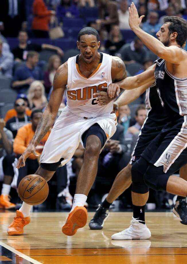Phoenix Suns' Channing Frye, left, drives past San Antonio Spurs' Marco Belinelli, of Italy, during the second half of an NBA basketball game, Wednesday, Dec. 18, 2013, in Phoenix. The Spurs won 108-101. (AP Photo/Matt York) Photo: Matt York, Associated Press