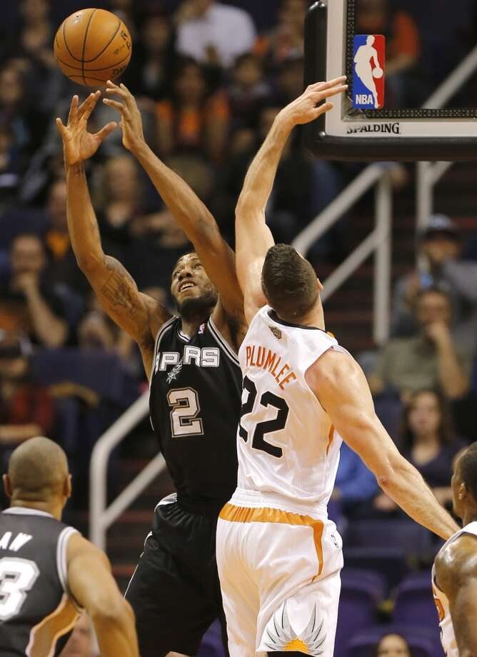 San Antonio Spurs' Kawhi Leonard (2) pulls down a rebound next to Phoenix Suns' Miles Plumlee (22) during the first half of an NBA basketball game, Wednesday, Dec. 18, 2013, in Phoenix. (AP Photo/Matt York) Photo: Matt York, Associated Press
