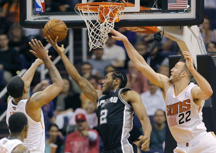 San Antonio Spurs' Kawhi Leonard (2) drives against Phoenix Suns' Miles Plumlee (22) during the second half of an NBA basketball game, Wednesday, Dec. 18, 2013, in Phoenix. The Spurs won 108-101. (AP Photo/Matt York) Photo: Matt York, Associated Press