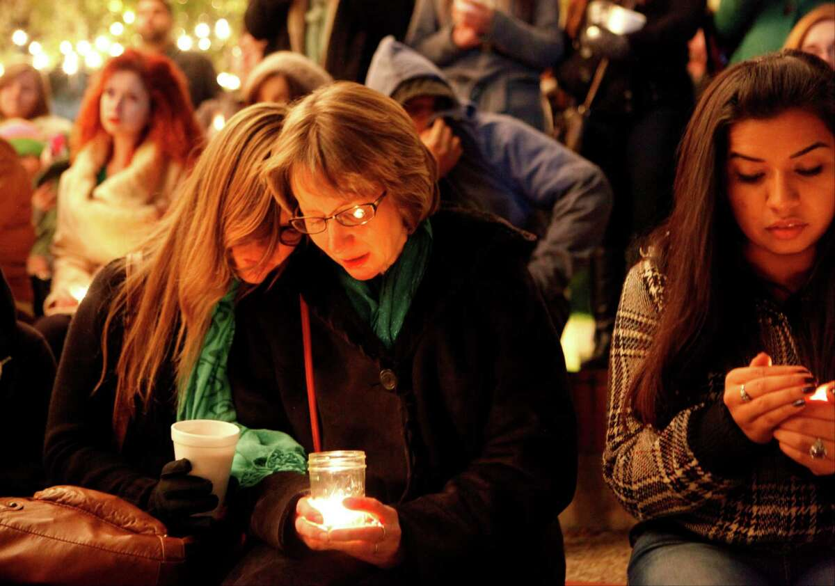 Valerie Redus (middle), mother of Robert Cameron Redus is hugged by Emily Vaughan, a friend of the family as people gather at the University of the Incarnate Word grotto as part of the vigil for Cameron. Cameron Redus was a student at UIW who was killed by a university police officer.