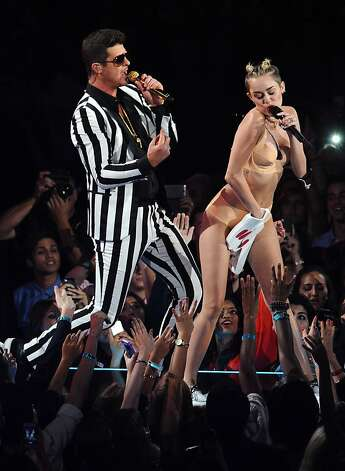 """Aug. 25: """"We Can't Stop"""" looking, no matter how much we try. Former TV tween queen Miley Cyrus appropriates (and revives) raver style for the MTV Video Music Awards and awkwardly twerks and grinds her way through giant teddy bears and Robin Thicke toward sex-pot-style relevance. OF the awards show, she later opines, """"I doubt they're ever gonna ask me back."""" Photo: Charles Sykes, Associated Press"""