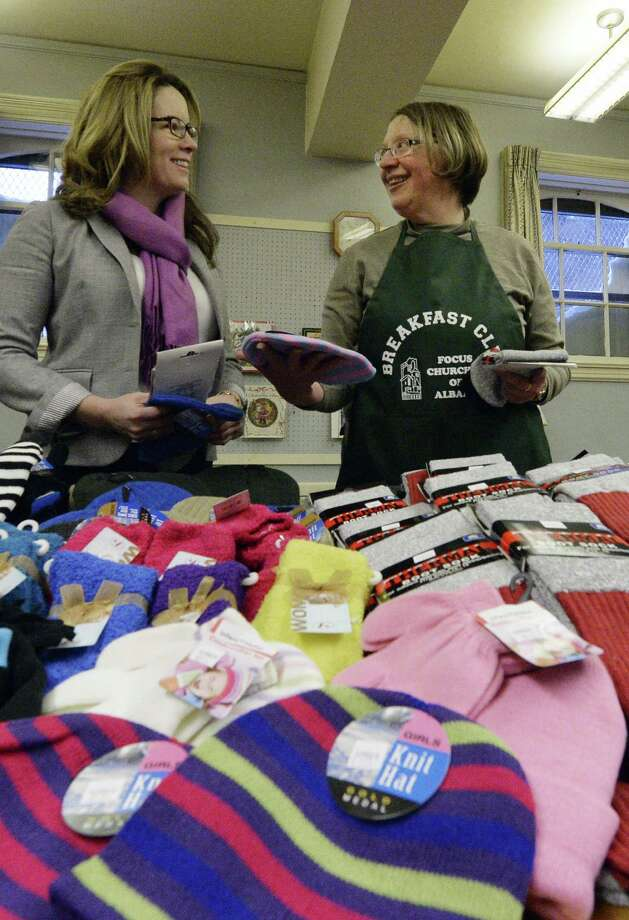 Kathy Leyden, manager of medical innovation at CDPHP, left, looks over some of the 250 hats, gloves, and socks that were donated by CDPHP to the FOCUS Winter Breakfast Program with Judy Henningson of Churches United in Inner-city Mission Wednesday morning, Dec. 18, 2013, at the Westminster Presbyterian Church in Albany, N.Y.  The clothing will be given to people in need during Christmas.  (Skip Dickstein / Times Union) Photo: Skip Dickstein / 00025080A