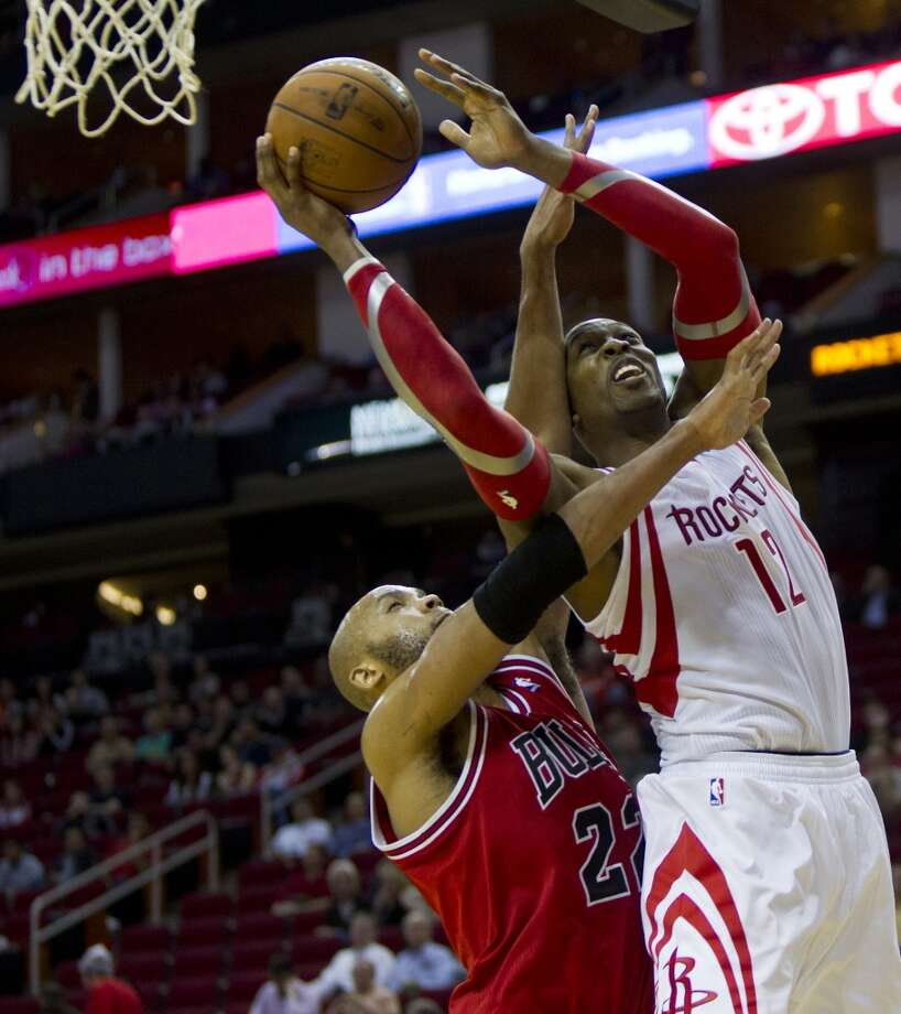 Rockets power forward Dwight Howard (12) drives to the basket under the pressure of Bulls power forward Taj Gibson (22). Photo: Marie D. De Jesus, Houston Chronicle